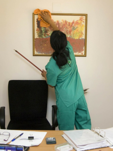woman in scrubs cleaning office picture